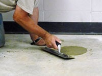 Repairing the cored holes in the concrete slab floor with fresh concrete and cleaning up the Maple Grove home.