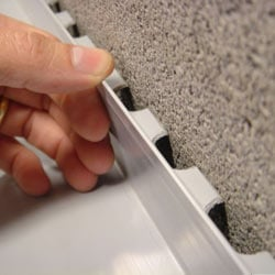 A contractor in La Crosse installing a perimeter drain tile system during a sump pump installation.
