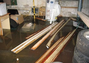 A severely flooding basement in Maple Grove, with lumber and personal items floating in a foot of water