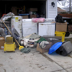 Soaked, wet personal items sitting in a driveway, including a washer and dryer in Zumbrota.
